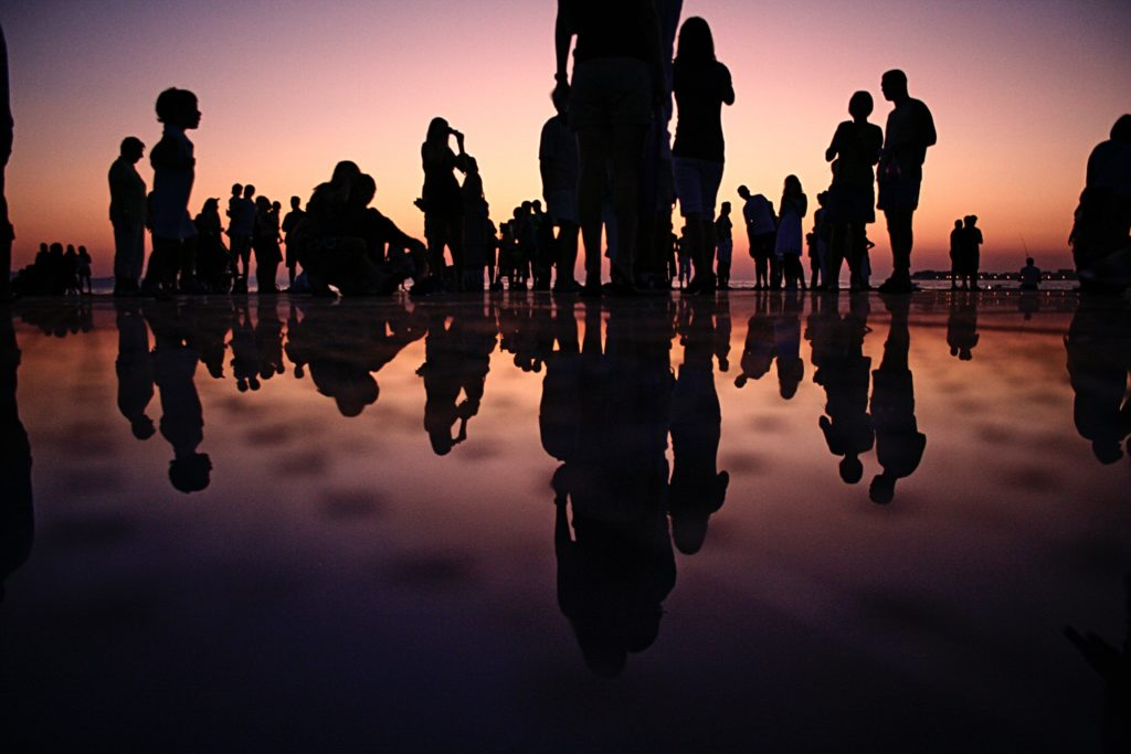 silhoutted group of people in perspective against dusk sky